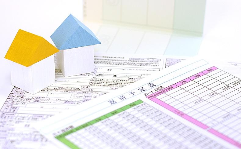 家の模型と通帳と返済予定表