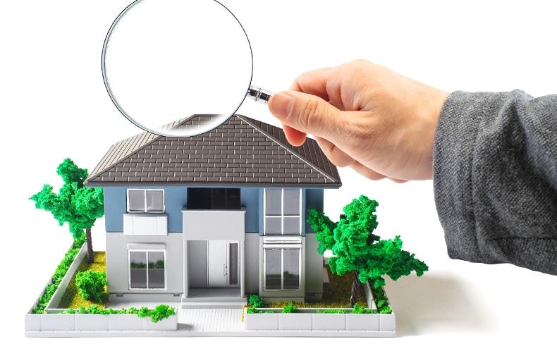 家の模型を虫眼鏡でチェックする手
