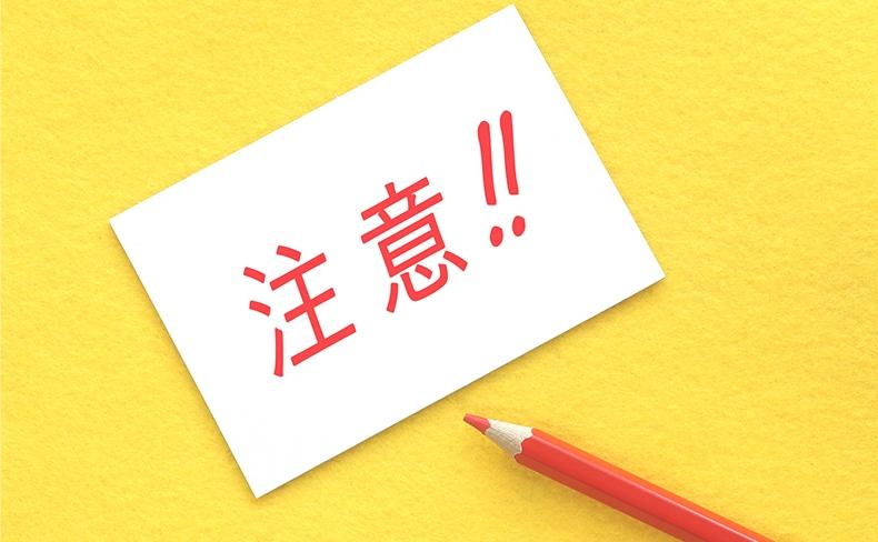 注意!!という文字が書かれた紙と赤い色鉛筆