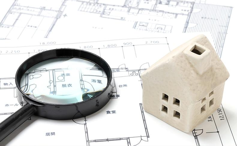 家の設計図と家の模型と虫眼鏡