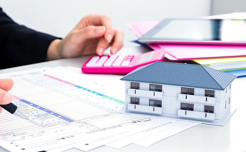 家の模型と確定申告の書類と電卓とバインダー