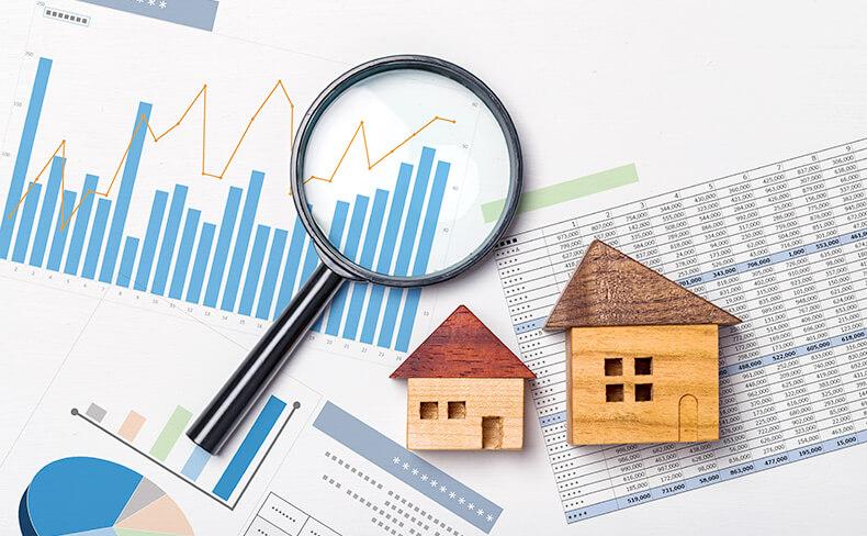 家の模型と虫眼鏡とグラフチャート