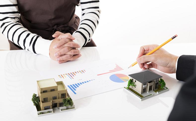 家の模型とグラフデータを挟んで相談する男女