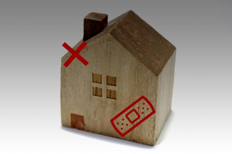 ×印が付き絆創膏が貼られた家の模型